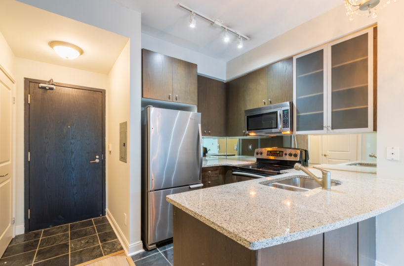 Rental Condo kitchen and suite entrance, fridge, microwave and sick are visible